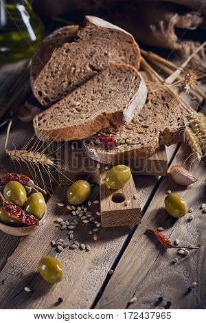 Fresh multigrain crusty bread green olives chilly pepper and wheat ears on a rustic wooden table. Bakery and grocery food store concept.