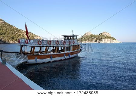 Pleasure boat near the pier on the shores of a blue lagoon in the Aegean Sea in Turkey.