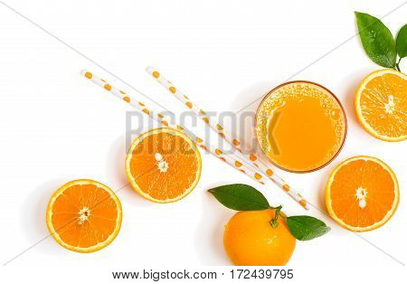 Top view of freshly squeezed orange juice with orange fruits with green leaves with drops of water isolated on white background.