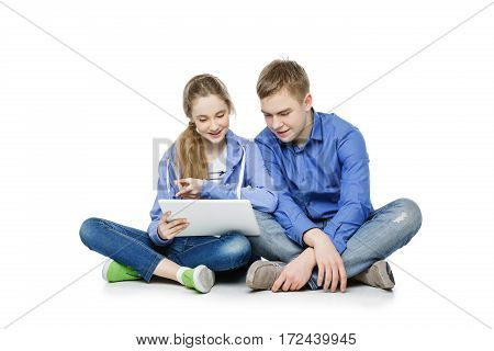 Beautiful happy teen age boy and girl in casual clothes looking at tablet. Brother and sister sitting on floor. Isolated on white background. Copy space.
