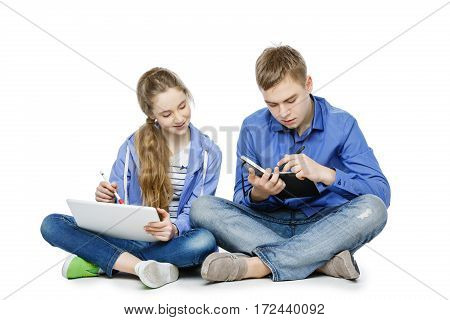 Beautiful teen age girl in casual clothes looking at tablet. Sad boy with paper notebook. Brother and sister sitting on floor. Isolated on white background. Copy space.