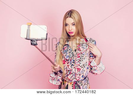Vogue young girl posing for selfie on the pink background. Horizontal outdoors shot.