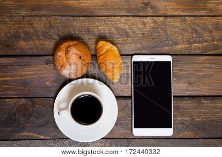 Mobile Phone With White Mug Of Coffee And Croissants