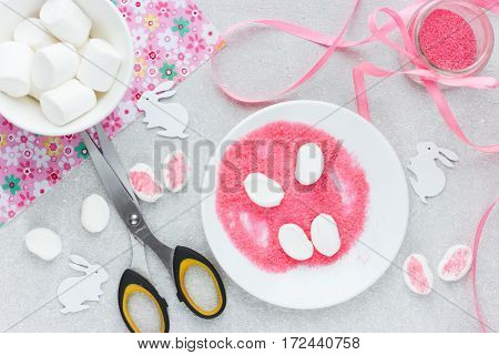 Easter bunny ears from pink colored sugar and marshmallow. Cooking Easter bunny cupcakes