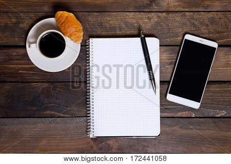View From Above. Mobile Phone With White Cup Of Coffee And Notepad On Wooden Background. Workspace F