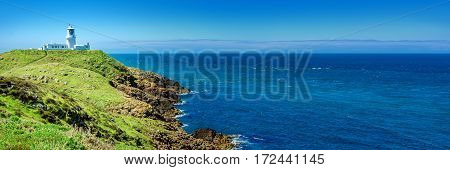Panorama: White lighthouse at the coast of South Wales.