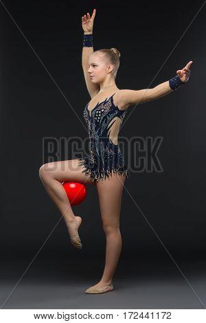 Beautiful blond gymnastist girl in black sparkling cistume holding red ball over black background