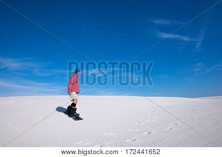 Man In Colorful Shirt Slides Down On A Snowboard On The Sand Dun