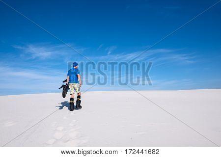 Man Training To Snowbord On The Sand Dune