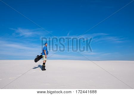 Happy Man With A Snowboard In Hands Stands In On The Sand Dune