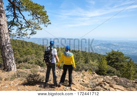 Couple of travelers are standing on the rocky and admiring stunning view - sunny day in the mountains. National park Troodos Cyprus. Back view.