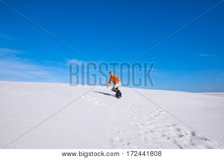 Guy Snowboarder Rides In The Sand Dunes