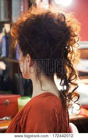 woman with raised long curly hair at hair studio side view closeup