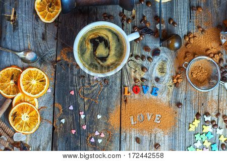 Black coffee in a cup on a gray wooden surface with chocolates and sweets