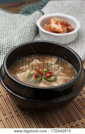 A close up of a popular Korean dish of Denjang soup and side kimchee.