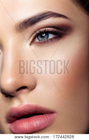 Close-up portrait of beautiful young woman with make-up. Beauty macro shot.