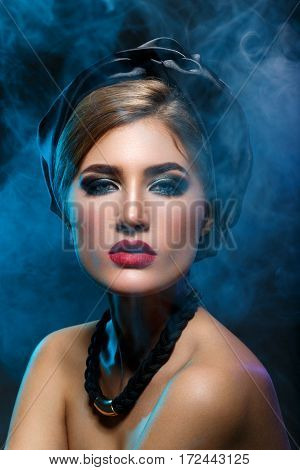 Beautiful young woman with bright makeup, red lips, black shawl on head and necklace. Studio beauty shot with blue smoke. Copy space.
