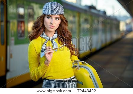 Pretty young woman at a train station (color toned image)