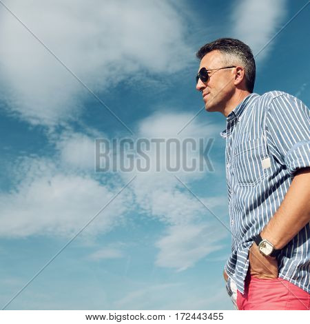 Handsome man. Outdoor male portrait. Middle-aged man, summer outdoor portrait over sky, image toned.