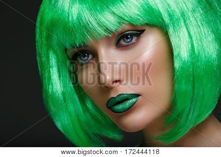 Beautiful young woman with glowing skin, fashion make-up in short green hair wig. Beauty shot on black background. Copy space.