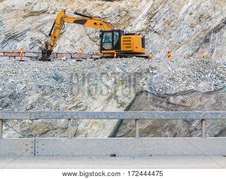 Industry. Heavy duty excavator machine digger bulldozer working on stone construction site Norway Scandinavia