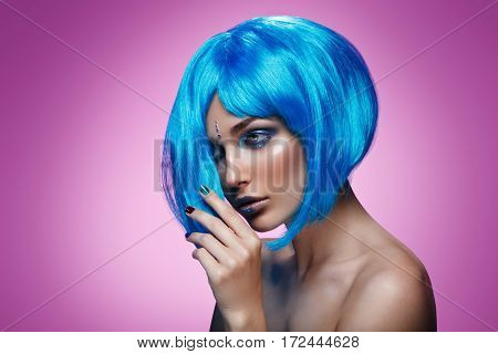 Beautiful young woman with glowing skin, fashion make-up and metallic nails in short blue wig touching hair. Beauty shot on magenta pink background. Copy space.