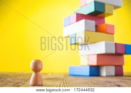 Business metaphor of businessman climbing colorful career stairs on yellow background. Going up concept using stairway of wood blocks. Achieving success. Business competition. Career social status.