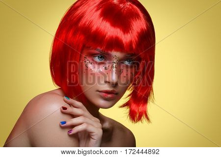 Beautiful young woman with glowing skin, fashion make-up and metallic nails in short red wig touching hair. Beauty shot on yellow background. Copy space.