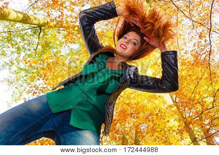 Nature outdoors concept. Ginger hair girl is playing around. Young beautiful lady is wearing green shirt jeans and leather jacket.