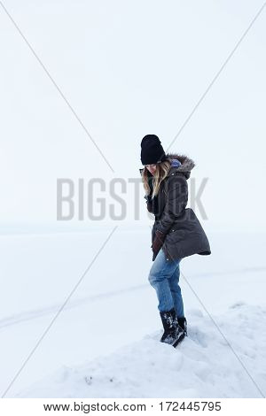 Girl on a background of a white field. She looks into the distance