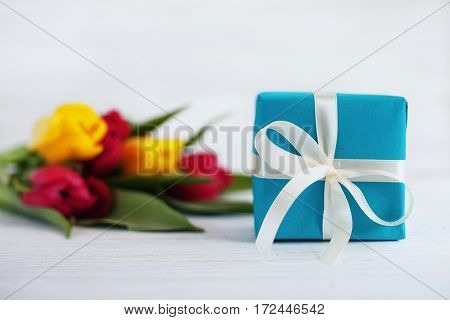 White wooden background tulips and gift. Concept of holiday birthday Easter March 8.