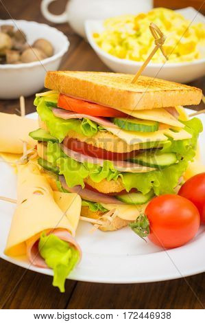 Big Sandwich, Meat, Lettuce, Cheese And Vegetables On Toasted. Wooden Background. Close-up