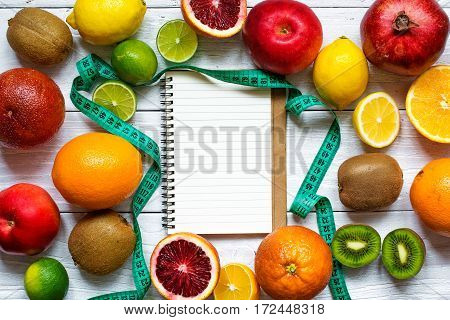 fresh fruits and vegetables for healthy diet on white wooden table. fitness concept with notebook and type measure. top view