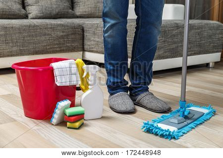 Cleaning service. Bucket with sponges, chemicals bottles and mopping stick. Rubber gloves, plunger and towel. Man standing in slippers.