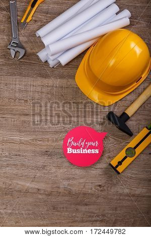 Adjustable wrench, hammer and building level. Build your business speech bubble. Architecture plans and helmet. Wood rustic background.