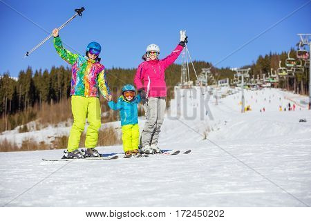 Cheerful family of three standing on ski parents lifting hands with ski poles