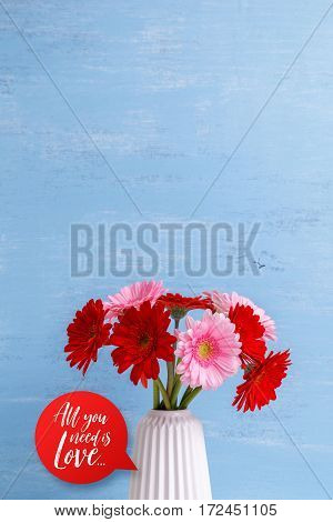 Gerbera flowers in vase on blue wood vintage background. 8 march or Valentines day love design. Fresh natural flowers. All you need is love.