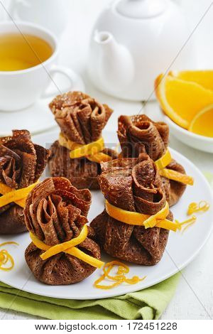 Chocolate pancakes with cup of tea and oranges