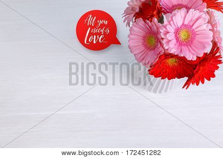Gerbera flowers in vase on white wood vintage background. 8 march or Valentines day love design. Fresh natural flowers. All you need is love.