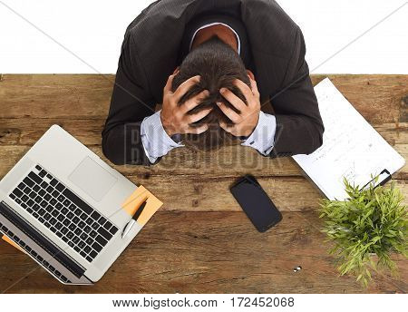 desperate stressed businessman sitting at office laptop computer desk with hands on his head crying devastated and frustrated in overwork and business crisis concept