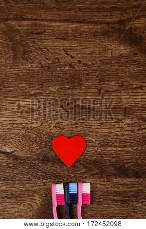 Lovers concept with heart and toothbrushes. Valentines day design on wood vintage background. Sexual relationships. Wooden rustic board.