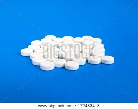 Many white pills on a blue background.