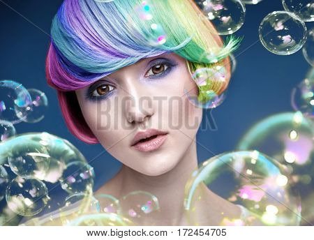 Color haired young woman with soap bubbles