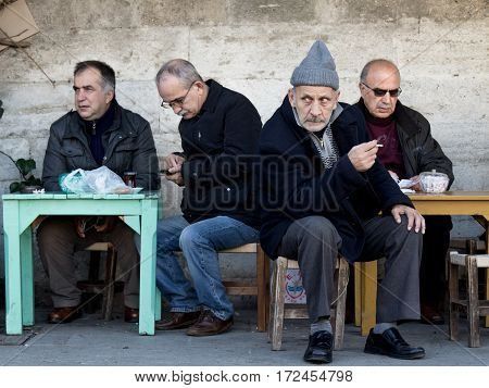 ISTANBUL, TURKEY - DECEMBER 28, 2015: Old Turkish men sitting at a cafe near Kadikoy district, on the Asian side of the city