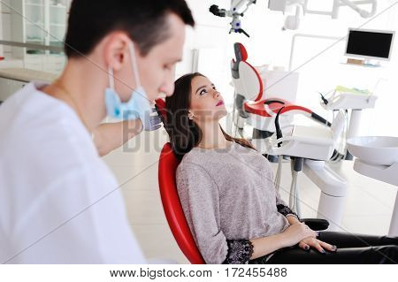 attractive girl in red dental chair at the reception of dentists. dentist prepares for a patient examination. Dentistry, teeth whitening, dental fillings, smile, tooth decay.