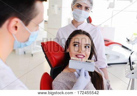 choose the color of the teeth. two dental pick the color of tooth enamel for the patient