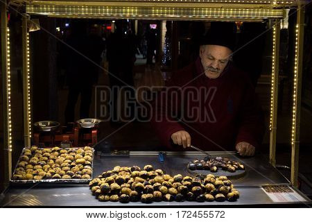 ISTANBUL TURKEY - DECEMBER 28 2015: Picture of an old chestnut seller on a cold winter evening on Istiklal street