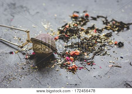 Tea herbs and spoons on grey stone background