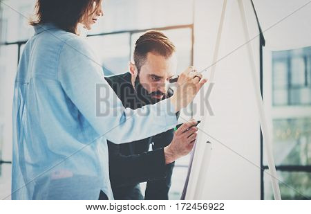 Teamwork and brainstorming concept.Young creative coworkers working with new startup project in modern office.Two colleagues writing on the presentation board.Horizontal, blurred background effect