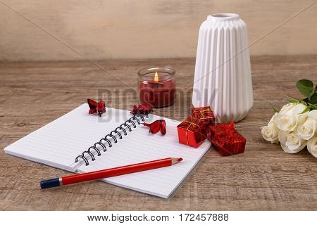 White roses with gift boxes and vase. Valentines day concept. Red pencil with notebook and candle. Love design. Wooden rustic board.